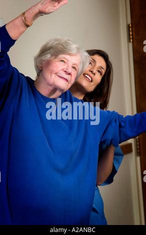 Nurse helping senior woman with exercising - Stock Photo