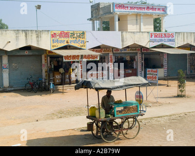 Typical street scene with young local man trading goods from street stall Madhya Pradesh India - Stock Photo