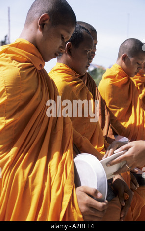 Cambodia. A young begging monk receiving a donation of rice in his begging bowl - Stock Photo