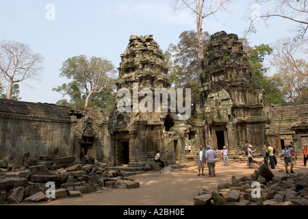 Cambodia Siem Reap Angkor Thom group Ta Prohm Buddhist Temple tourists in courtyard surrounding central sanctuary - Stock Photo