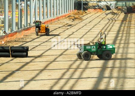 Construction  large new warehouse development building site dumper truck machine working below unclad steelwork - Stock Photo