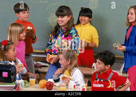 Group of children of all ethnic groups having school lunch together - Stock Photo