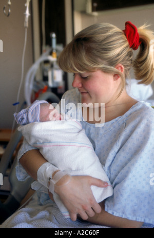 Close-up of teenage mother holding newborn baby - Stock Photo