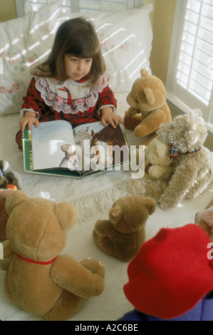 Vertical shot of young girl sitting on her bed reading to her stuffed animals - Stock Photo