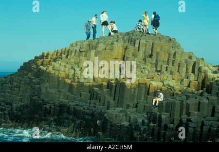 people standing on basalt columns at Giants Causeway in County Antrim in Northern Ireland - Stock Photo