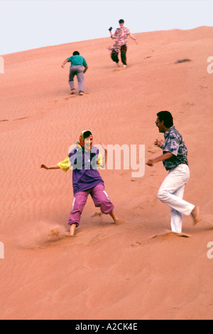 Oman. Wahiba Sands. Tourists visting the Wahiba Sands in the interior. Climbing and sliding down sand dunes is great - Stock Photo