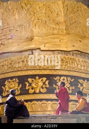 Tibetan monks and pilgrim under giant prayer wheel Shangri La China - Stock Photo