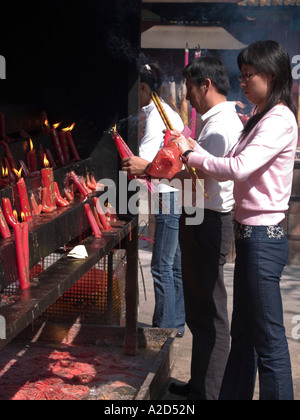 lighting candles and incense at a Taoist temple in Kunming Yunnan China - Stock Photo