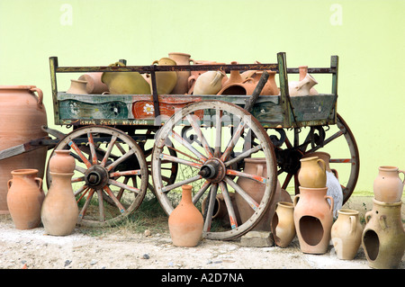 A display of clay pots on an old wooden wagon for sale in Cappadocia, Turkey. - Stock Photo