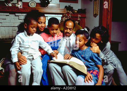 African American parents age 38 and 40 reading bible to kids, ages 5 through 15. St Paul Minnesota USA - Stock Photo