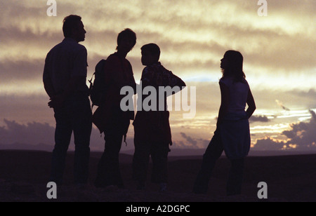 Family of four silhouetted against sunset, Morocco - Stock Photo