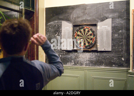 Man playing traditional game of darts in pub, London, England UK - Stock Photo
