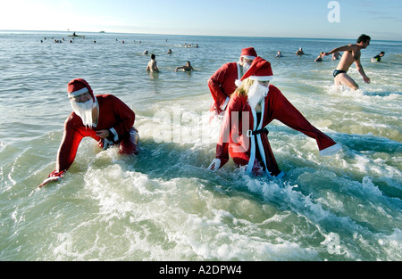 Hardy swimmers dressed in Santa suits take part in the annual Christmas Day Dip in the sea at Brighton on a sunny - Stock Photo