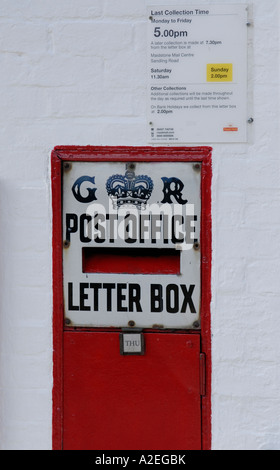 Red letter box set in a white painted brick wall with a black and white enamel sign saying GR Post Office Letter - Stock Photo
