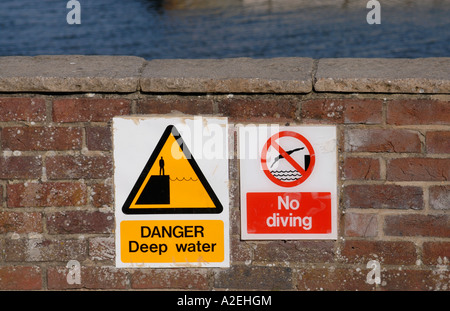 Signs saying Danger Deep Water and No Diving on a wall at the side of Lymington Harbour - Stock Photo