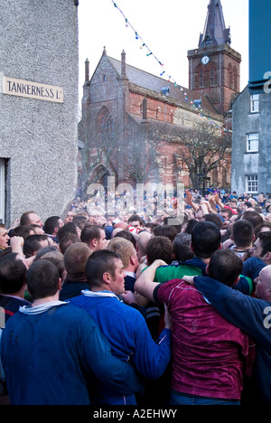 dh The Ba KIRKWALL ORKNEY Pack of Ba players and St Magnus Cathedral New Years day ball game - Stock Photo