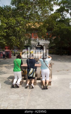 dh Po Lin Monastery LANTAU HONG KONG Worshippers on knees at joss stick urn entrance to temple worship people - Stock Photo
