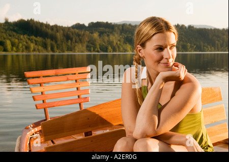 Young woman sitting on rowing boat in lake Stock Photo
