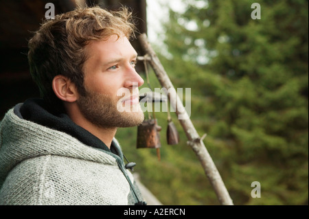 Young man in front of hut - Stock Photo