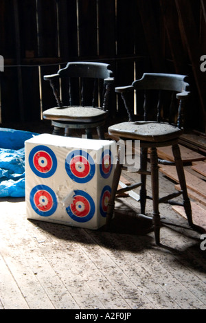 Bar stools beside targets in barn attic. 'Blue River' Wisconsin USA - Stock Photo