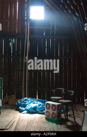 Bar chairs beside targets in barn attic. Blue River Wisconsin USA - Stock Photo