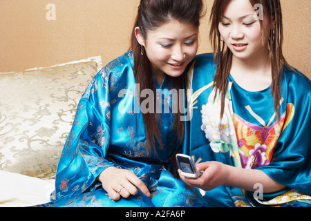 Close-up of a young woman sitting with a teenage girl looking at a mobile phone - Stock Photo