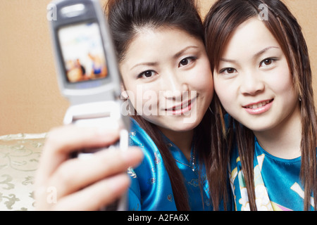 Portrait of a young woman with a teenage girl taking a photograph of themselves Stock Photo