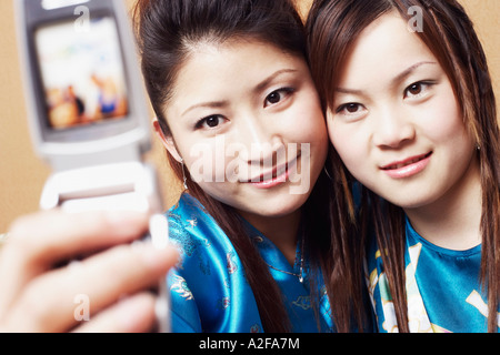 Close-up of a teenage girl and a young woman taking a photograph of themselves Stock Photo