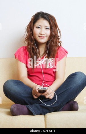 Portrait of a young woman listening to music - Stock Photo