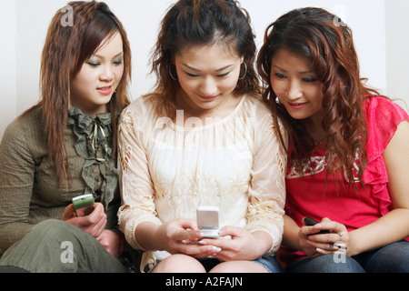 Close-up of three young women looking at a mobile phone - Stock Photo