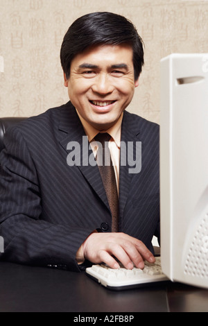Portrait of a businessman working on a computer in an office - Stock Photo