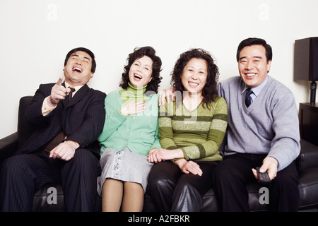 Portrait of two mature couples sitting together on a couch smiling - Stock Photo