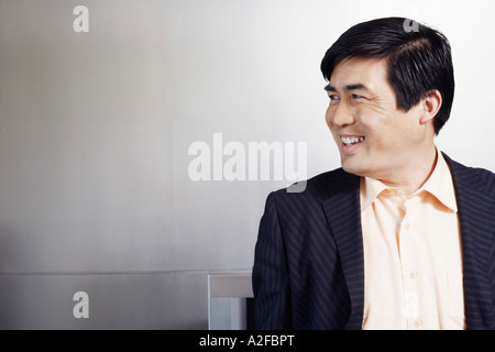 Close-up of a businessman looking sideways smiling - Stock Photo