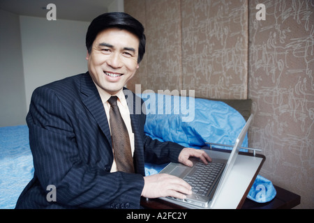 Portrait of a businessman sitting on the bed smiling - Stock Photo