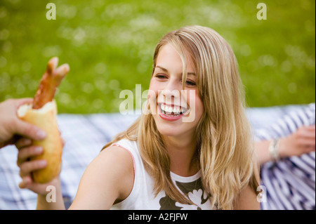 Young woman taking grilled sausage, portrait - Stock Photo