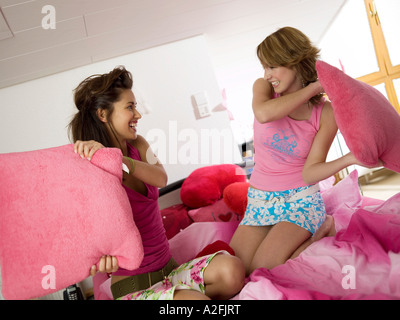 Two teenage girls having pillow fight - Stock Photo