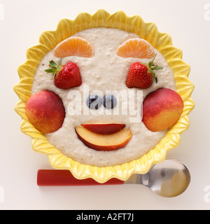 A smiling fruit face on a bowl of porridge - Stock Photo