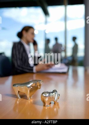 Figurines of bull and bear on desk (focus on foreground) - Stock Photo
