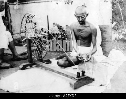 Mahatma Gandhi sitting on charkha spinning wheel and spinning cotton thread at Sabarmati Ashram in Gujarat India - Stock Photo