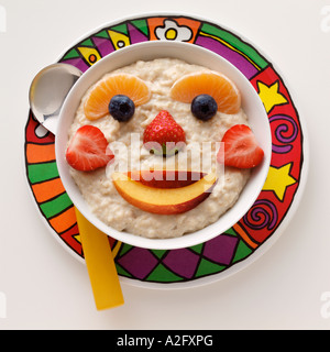 A smiling fruit face in a bowl of porridge - Stock Photo