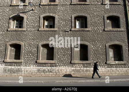 323 a young french male walks in front of the facade of an old warehouse - Stock Photo