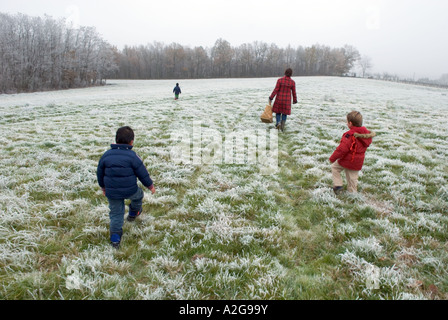 three young boys and their mum walk across a frost covered field away from camera - Stock Photo