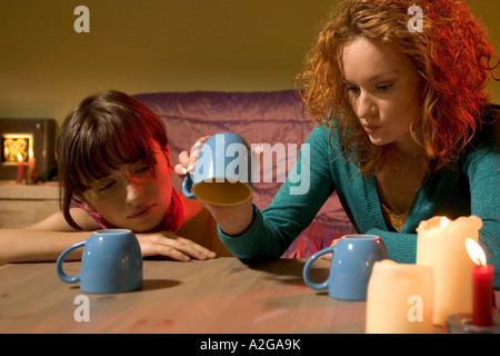 1214819 indoor flat room young woman women blonde curly hair brunette fringe 20 25 girl girls friend friends table hold b