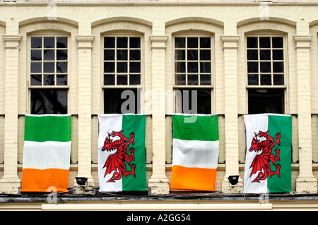 Welsh and Irish flags hanging from windows outside a pub in Cardiff city centre Wales UK - Stock Photo