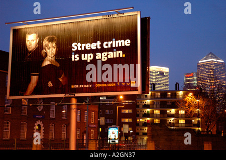 Giant billboards advertising television programme set against cityscape of docklands. - Stock Photo
