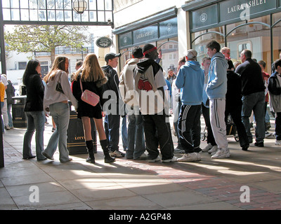 teenage boys and girls hanging out in a shopping centre - Stock Photo