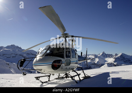 An alpine rescue helicopter lands on the Les Carroz Flaine Grand Massif in the Savoie region of the French Alps - Stock Photo