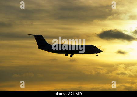 British Airways Avro RJ 100 aircraft landing at Birmingham International Airport at sunset, West Midlands, England, - Stock Photo