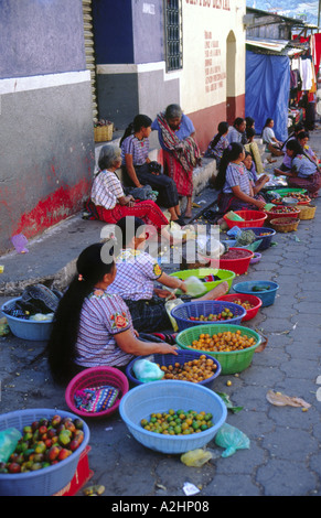 Women selling fruit and vegetables at a small market in Santiago de Atitlan on Lake Atitlan in Guatemala - Stock Photo