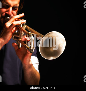 Square shot of man playing trumpet on a black background - Stock Photo